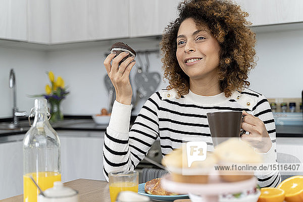 Woman sitting in kitchen  having breakfast
