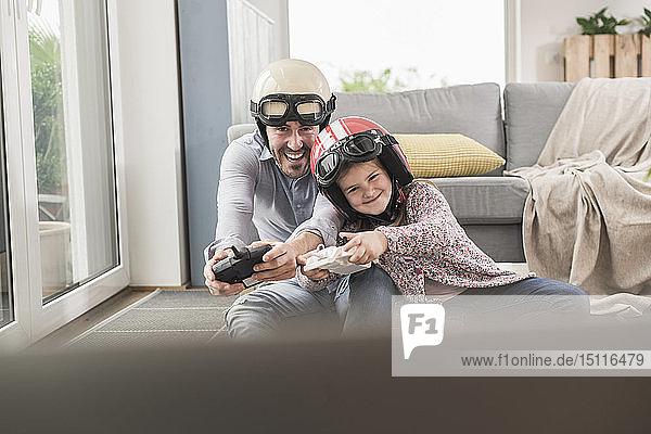 Junger Mann und kleines Mädchen tragen Bikerhelme  spielen Rennspiel mit Spielkonsolen