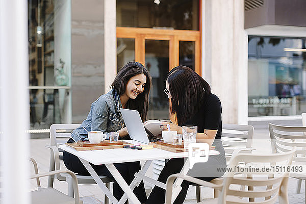 Zwei Freunde sitzen zusammen mit Buch und Laptop in einem Straßencafé