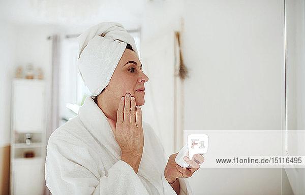 Reife Frau im häuslichen Badezimmer mit Feuchtigkeitscreme