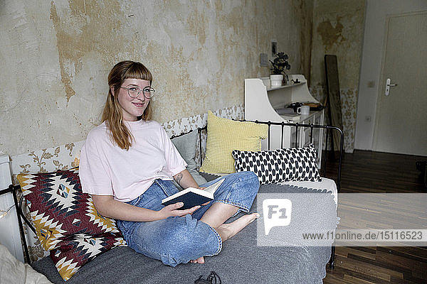 Female student reading a book in her room