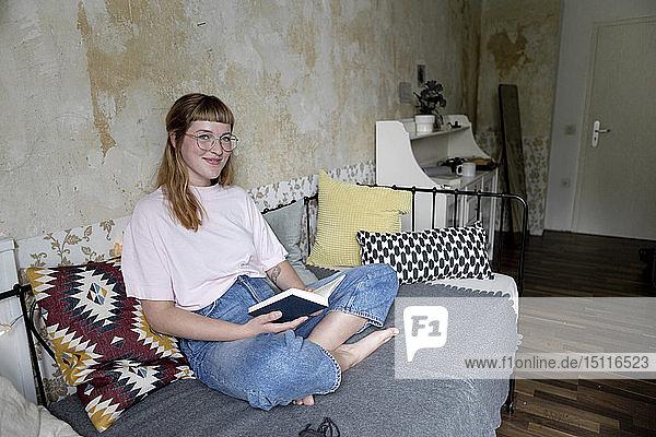 Studentin liest in ihrem Zimmer ein Buch