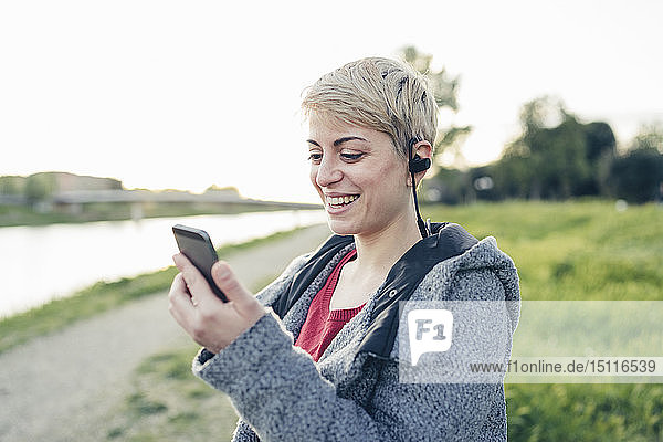 Porträt einer glücklichen jungen Frau  die ein Smartphone und Headset im Freien benutzt