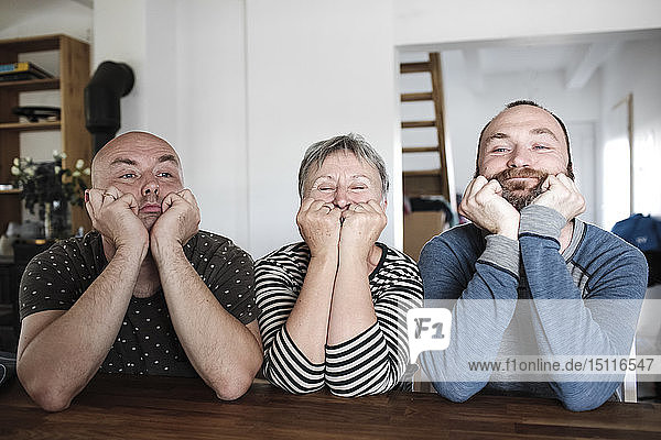Porträt von erwachsenen Söhnen mit älterer Mutter  die zu Hause mit dem Kopf in der Hand am Tisch sitzt