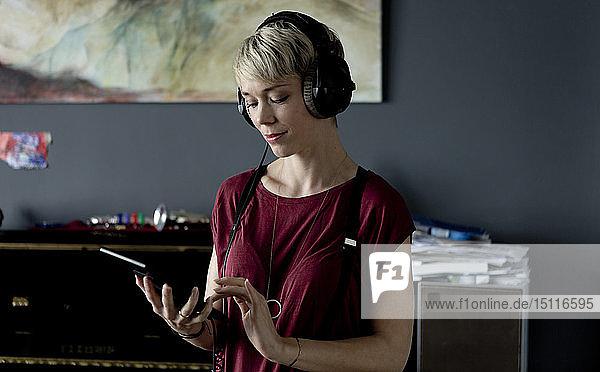 Porträt einer blonden Frau  die mit Kopfhörer und digitalem Tablet Musik hört