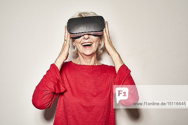 Portrait of laughing mature woman wearing Virtual Reality Glasses