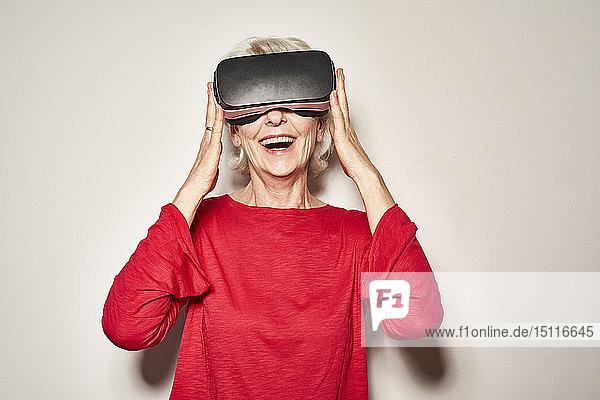 Porträt einer lachenden reifen Frau mit Virtual-Reality-Brille
