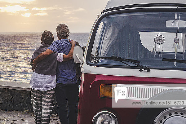 Senior couple traveling in a vintage van  looking at the sea with arms around