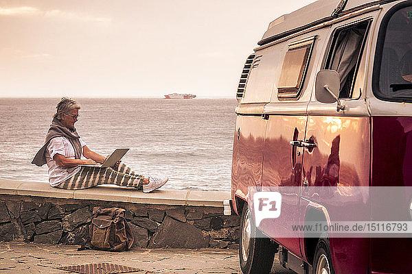 Ältere Frau  die mit einem Oldtimer-Van reist  auf einer Mauer am Meer sitzt und einen Laptop benutzt