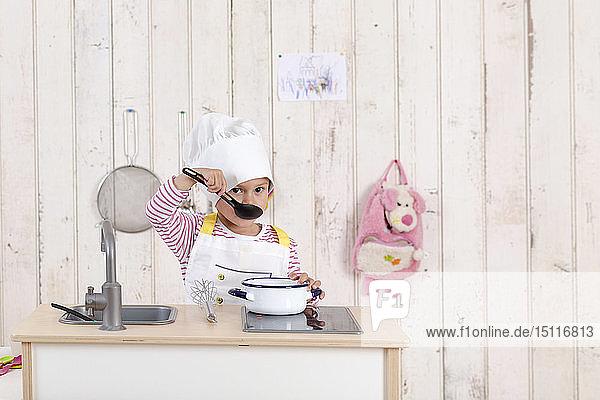 Porträt eines kleinen Mädchens beim Spielen mit der Spielzeugküche