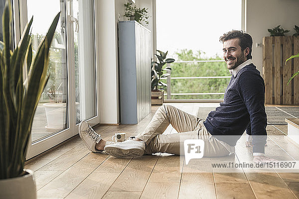 Young man sitting on floor  looking out of window  relaxing