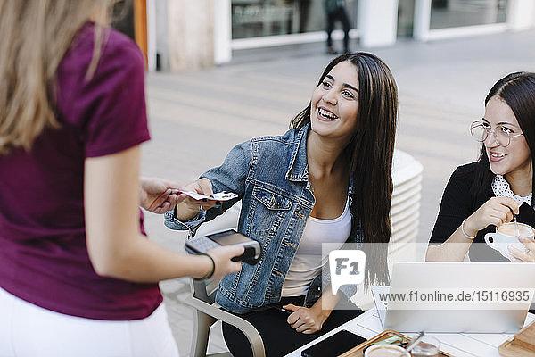 Junge Frau bezahlt in einem Café