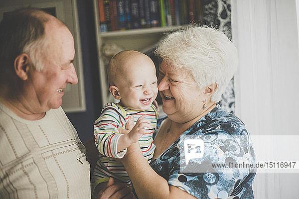Glückliche Großeltern halten ihren kleinen Enkel
