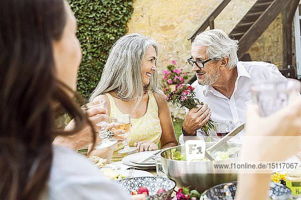 Fröhliche Familie beim gemeinsamen Essen im Garten