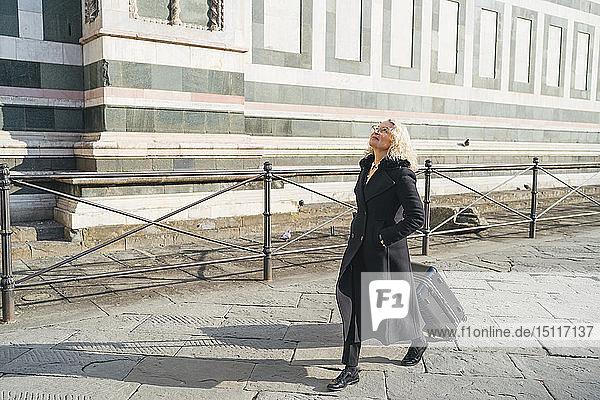 Italien  Florenz  reife Geschäftsfrau in schwarzem Mantel  die mit einem Rollkoffer durch die Stadt läuft