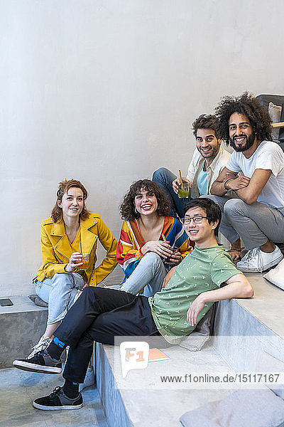 Portrait of group of friends sitting on stairs having a drink