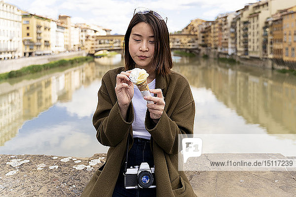 Italy,  Florence,  young tourist woman eating an ice cream cone at at Ponte Vecchio