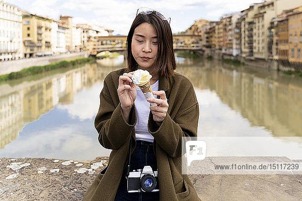 Italien,  Florenz,  junge Touristin beim Essen einer Eistüte in Ponte Vecchio