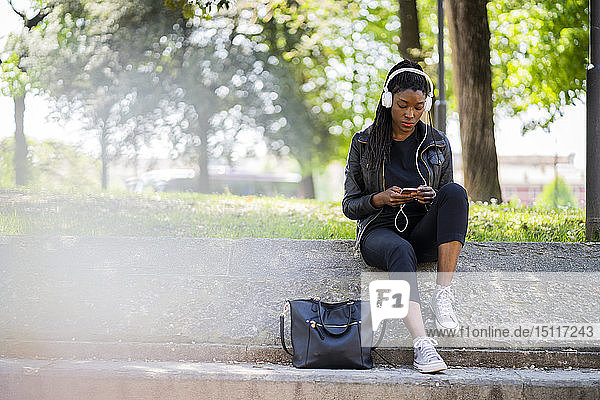 Woman resting in urban park with cell phone and headphones