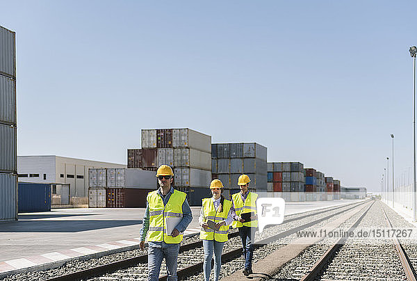 Arbeiter gehen gemeinsam auf Eisenbahnschienen in der Nähe von Frachtcontainern auf einem Industriegelände