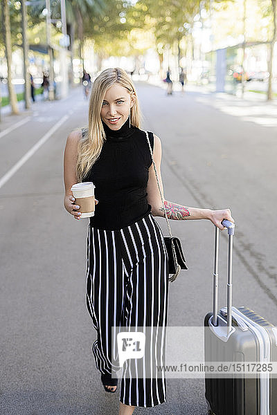 Porträt einer lächelnden blonden Frau mit Kaffee zum Mitnehmen und Rollgepäck auf der Straße