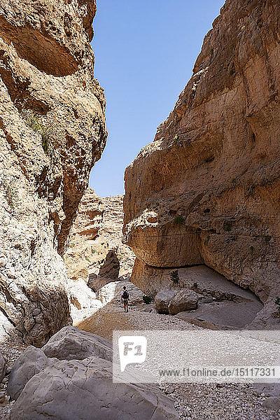 Man walking through rocks  Wadi Bani Khalid  Oman
