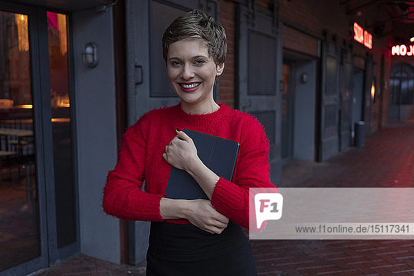 Germany  Berlin  portrait of happy businesswoman with digital tablet outdoors