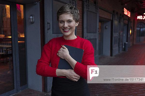 Deutschland  Berlin  Porträt einer glücklichen Geschäftsfrau mit digitalem Tablet im Freien
