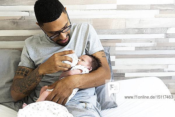 Vater füttert sein Neugeborenes mit der Flasche im Bett