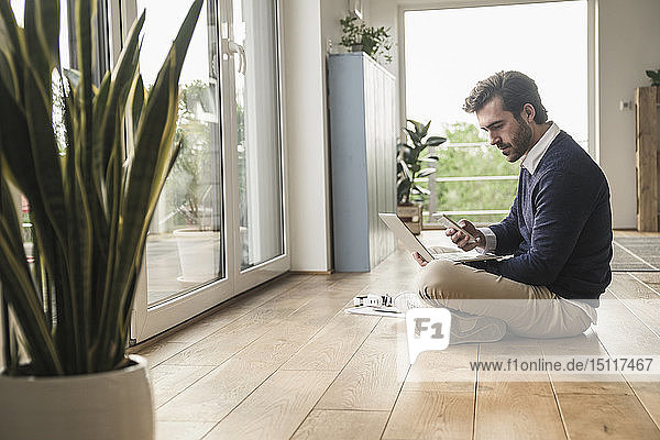 Young man sitting cross-legged in front of window  using laptop