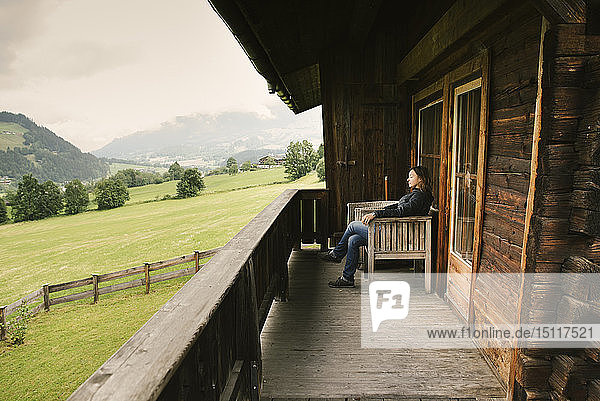 Woman sitting on balcony of rustic house  Jochberg  Austria