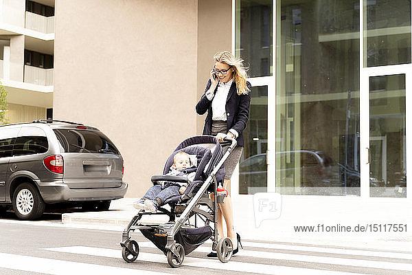 Lächelnde junge Geschäftsfrau am Telefon auf der Straßenkreuzung mit einem kleinen Jungen im Kinderwagen