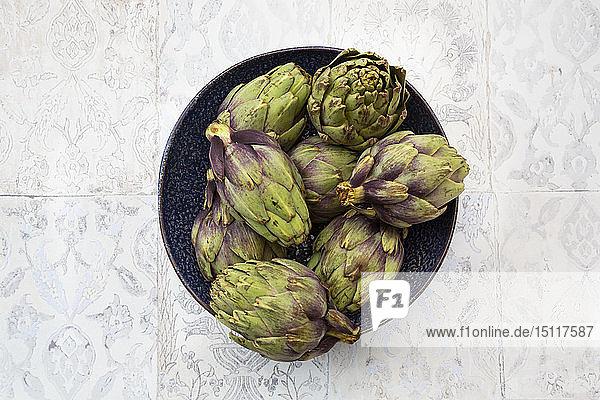 Italian bio artichokes in bowl  from above