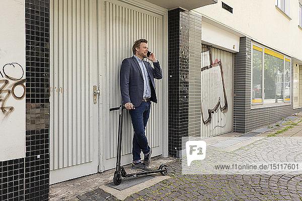 Geschäftsmann mit E-Scooter am Telefon