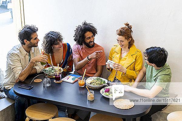 Gruppe glücklicher Freunde mit einer Sofortbildkamera beim Mittagessen in einem Restaurant