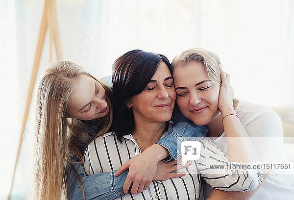 Besuch von Töchtern  die ihre Mutter umarmen