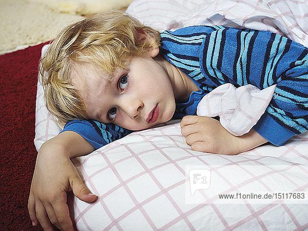 Porträt eines kleinen Jungen auf dem Boden liegend mit Bettzeug