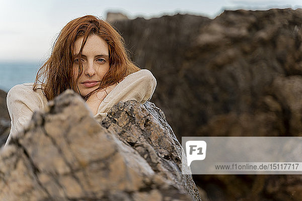 Portrait of redheaded young woman with nose piercing leaning on a rock