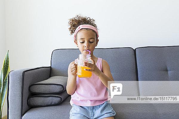 Mädchen  das zu Hause auf dem Sofa sitzt und etwas trinkt