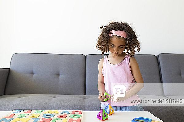 Mädchen spielt mit Lernspiel zu Hause