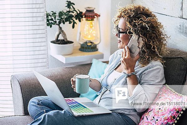 Woman on couch at home with coffee mug  laptop and cell phone