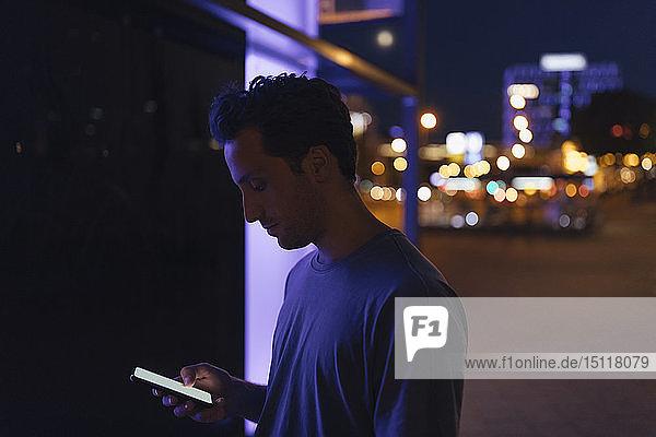 Junger Mann telefoniert nachts in der Stadt mit dem Handy