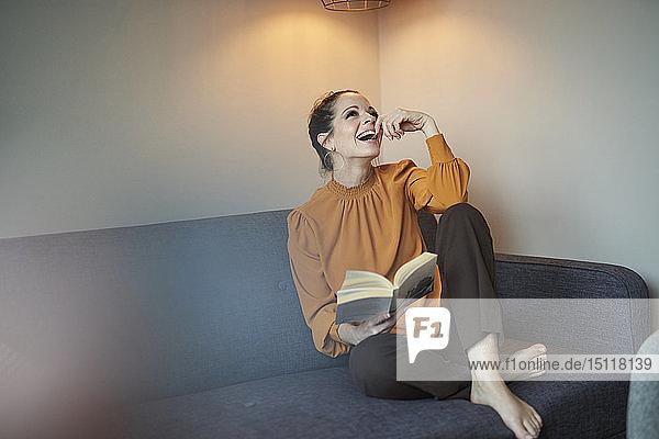 Lachende Frau mit Buch  die zu Hause auf der Couch sitzt