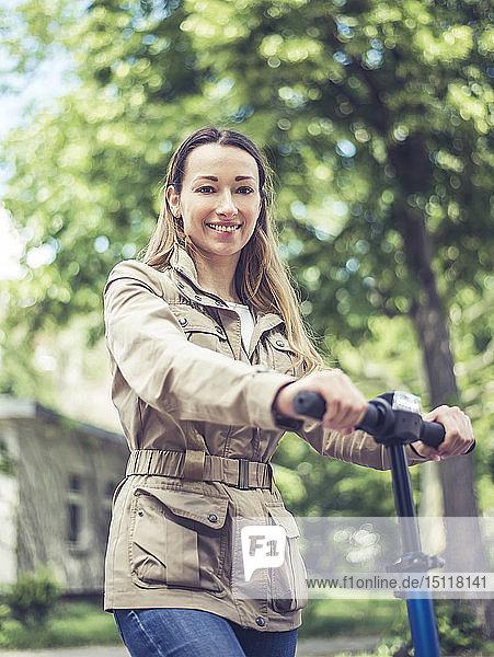 Porträt einer lächelnden Frau mit E-Scooter