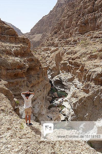 Mann genießt die Aussicht über Wadi Shab  Oman