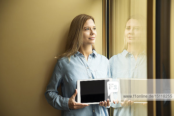 Geschäftsfrau hält Tablette und schaut aus dem Fenster