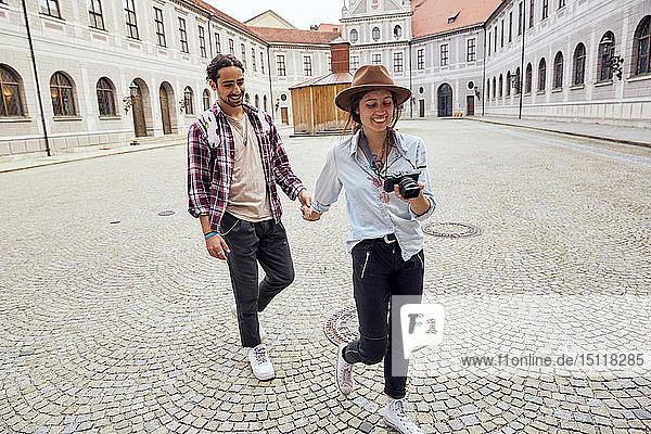 Young tourist couple walking in courtyard of Munich Residenz  Munich  Germany