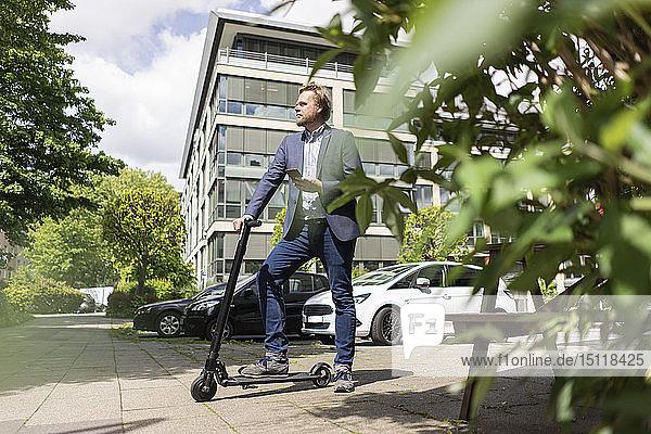 Geschäftsmann steht mit E-Scooter und Smartphone auf dem Bürgersteig in der Stadt