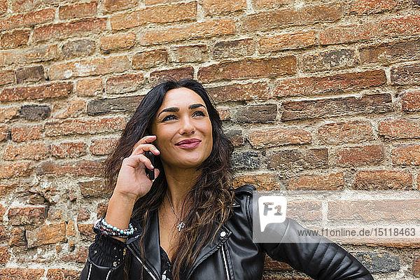 Porträt einer jungen Frau in schwarzer Lederjacke  mit Smartphone  im Hintergrund Backsteinmauer