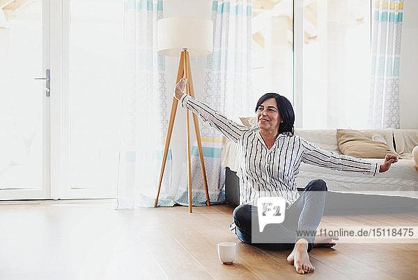 Reife Frau sitzt zu Hause auf dem Boden und entspannt sich bei einer Tasse Kaffee